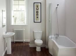 white bathtub with glass panel and white toilet bowl also white
