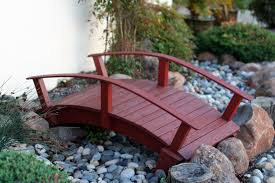 small wooden bridge garden with pebbles reaching pond