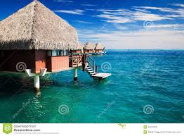 over water bungalow with steps into clear ocean royalty free stock