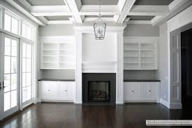 double white wooden shelving around black fireplace and four