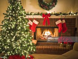 decorated christmas tree blazing fire in fireplace stockings