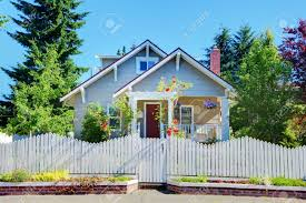cute small grey old craftsman style house with white fence stock