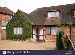 chalet bungalow home with ivy growing on the wall and gravel
