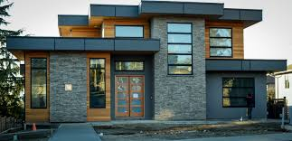 modern home with grey stone and cedar and black trim exteriors