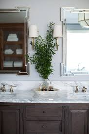 what color goes with brown bathroom cabinets chocolate brown bath cabinets with brass wall sconces