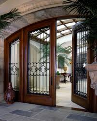 cool arched front doors with black trellises and wooden frame