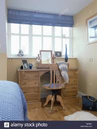 blue blind on window above old hand stripped wooden desk and chair
