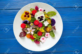 edible flower garnish edible flowers salad in a plate on blue wooden table stock photo