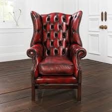 red leather wingback chair with wooden floor and white wall for