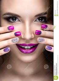 beautiful with a bright evening make up and purple manicure