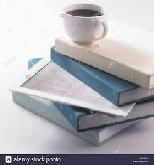 top of coffee cup a cup of coffee on top of a pile of books and a tablet stock photo