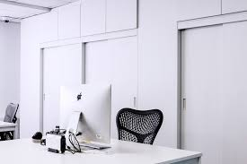 black mesh office rolling chair beside white wooden desk with
