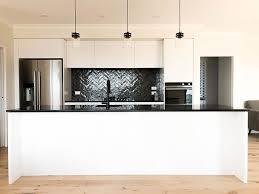 white kitchen cupboards black bench precision homes nz