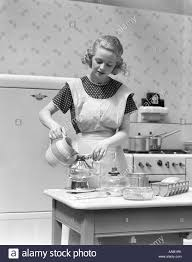 1930s woman in kitchen wearing apron making breakfast pouring