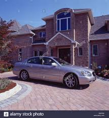 build a new car silver car on paved drive in front of new build traditional brick