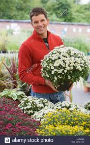 man in red top shopping for flowers in garden centre holding pot