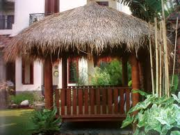 square wooden gazebo with thatched roof and side panels for small