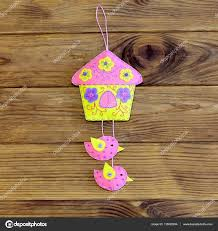 bright house with birds ornament isolated on wooden background