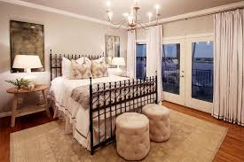iron scroll bed with rug under half the bed transitional bedroom