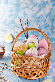 Decorated Easter Cookies in wooden basket on a blue wooden