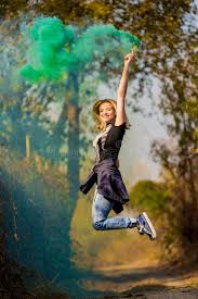 happy green color happy girl laughing and running with green color smoke bomb in