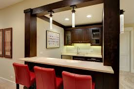basement bar with wooden cabinetry and columns and a paint grade