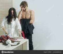 homme nu cuisine heureuse fille repassage des chemises comme pour
