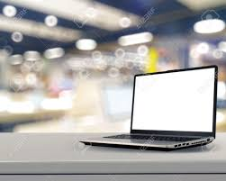 laptop with blank screen on white desk with blurred background