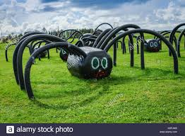 large halloween spider decoration made with a large covered hay