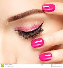 closeup woman face with pink nails near eyes stock photo image