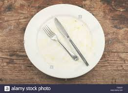 a dirty plate with a knife and fork stock photo royalty free