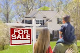 curious family facing for sale real estate sign and beautiful