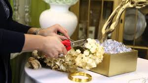 attaching silk flowers on branch centerpieces wedding decor