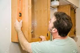 carpenter installing solid maple kitchen cabinets using a level
