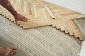carpenter on work putting wood floor parquet pieces home