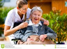 Home Nurse by Senior Woman In Nursing Home With Nurse In Garden Stock Photo