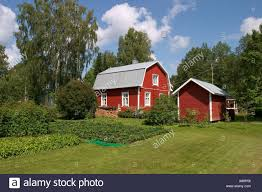 old fashioned traditional finnish red wooden house and garden