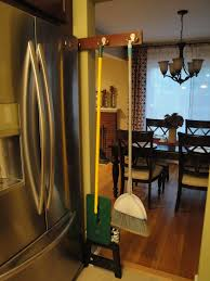 diy sliding broom holder fits in narrow space next to fridge made