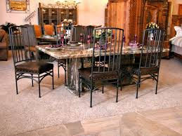 rectangle brown granite dining table and black iron chairs with