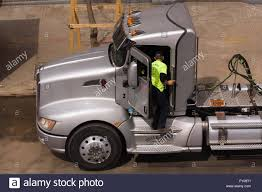 big kenworth trucks owner operator truck driver standing at the open door of a