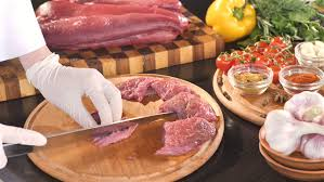 meat cutting table tops cook cutting meat on a board and fresh raw vegetables on a dark