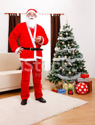 santa claus standing in front of christmas tree stock photos