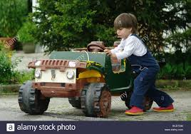kid play car little boy pushing a large electric toy car outside child age 3