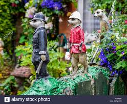 meerkat ornaments policeman and fireman on a wall in a