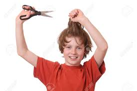 cutting boy hair with scissors young boy cutting his hair with scissors stock photo picture and