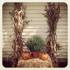Fall Decorating with hay bales pumpkins mums and corn stalks