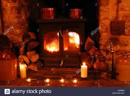 a fire inside a woodburner with logs and candles in the fireplace