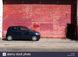Large Garage by Small Dark Blue Car Parked Against A Red Large Garage Door London