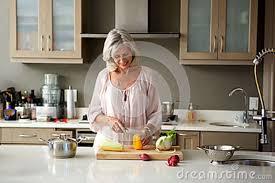 femmes plus cuisine une femme plus âgée préparant la nourriture pour un repas dans la