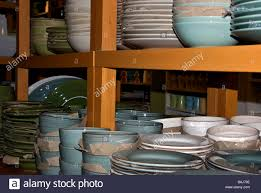 stacks of porcelain dinner plates and bowls on display for